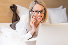 Business woman working in bed Stock Image