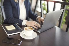 Business woman indoor with coffee and laptop on wooden table royalty free stock images