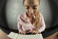Business woman is working on computer, looks at keyboard stock photo