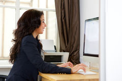 Business woman working on computer in office Royalty Free Stock Image