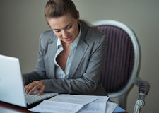Business woman working with documents and laptop. At hotel room royalty free stock photo