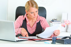 Business woman working with financial documents. Concentrated modern business woman sitting at office desk and working with financial documents Stock Image
