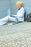 Business woman working on floor in background Royalty Free Stock Image