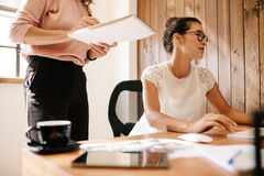 Business woman working at her desk with female colleague. Business women working at her desk with female colleague standing by with notepad. Two female office Royalty Free Stock Photography