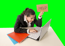 Business woman working on her  laptop holding a help sign  on green chroma key. Overworked woman wearing a business suit working on her  laptop holding a help Stock Photo