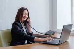Business woman working on her laptop and talking on the phone stock image