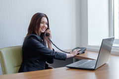 Business woman working on her laptop and talking on the phone royalty free stock photo