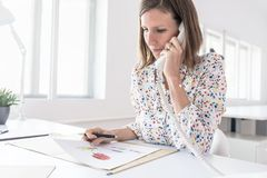 Business woman working at her office desk making a phone call Royalty Free Stock Photo