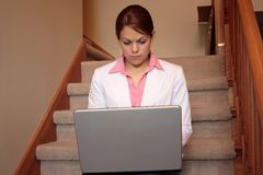 Business woman working at home on her laptop. Sitting on the stairs Stock Image