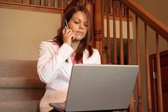 Business woman working at home on her laptop. Sitting on the stairs Stock Images