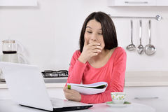 Business woman working at home. Business woman working on laptop computer at home. tired young woman in the kitchen royalty free stock photos