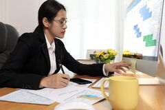 Free Business Woman Working In Office Looking And Check Paper Note. Business People Analysis Scheduler Data On PC Screen. Business Stock Photo - 195075600