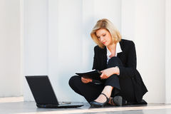 Business woman with a folder using laptop outdoor Stock Photos