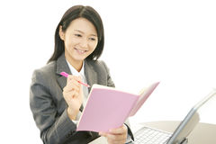 Business woman working on laptop. Asian business woman sitting at desk working on laptop Royalty Free Stock Photos