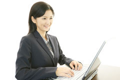 Business woman working on laptop. Asian business woman sitting at desk working on laptop Stock Photo