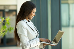 Business woman working laptop. Attractive black business woman working on laptop in office Royalty Free Stock Image