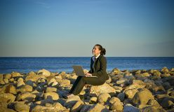 Business woman working on laptop at the beach royalty free stock images