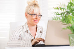 Business woman working at laptop. Beautiful mature Business woman working at laptop in the office Royalty Free Stock Photo