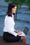 Business woman working with laptop in city park Royalty Free Stock Photography