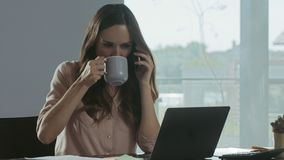 Business woman working at computer at workplace. Portrait of lady talking phone. Business woman working at laptop computer at remote workplace. Portrait of stock footage