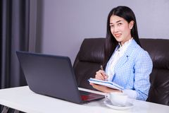 Business woman working with laptop computer and writes a journal Royalty Free Stock Photography