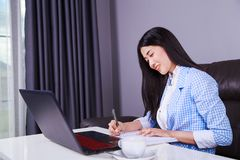 Business woman working with laptop computer and writes a journal Royalty Free Stock Images