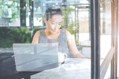 Business woman working with a laptop computer and writing notebo stock image