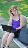 Business woman working on laptop - disability. Portrait of attractive blonde business woman who is missing part of left arm (congenital amputation) talking on stock images