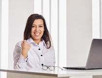 Business woman working on a laptop. She is happy. Beautiful business woman working on a laptop. She is happy Stock Image