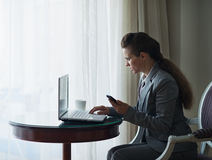 Business woman working on laptop in hotel room Stock Image