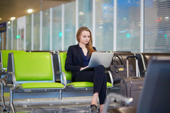 Business woman working on laptop in international airport. Young elegant business woman with hand luggage in international airport terminal, working on her Stock Images