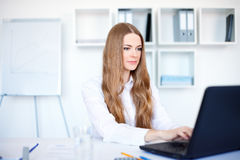 Business woman working on a laptop at office. Portrait of beautiful young smiling business woman working on a laptop at office Stock Image