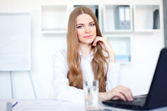 Business woman working on a laptop at office. Portrait of beautiful young smiling business woman working on a laptop at office Royalty Free Stock Photo