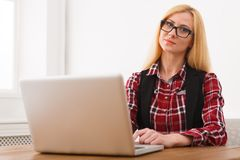 Business woman working on laptop at office. Businesswoman in eyeglasses typing something on computer while sitting at her working place, copy space royalty free stock photos