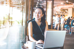 Business woman working on a laptop in the office. She looked at the window and smiled happily Royalty Free Stock Photography