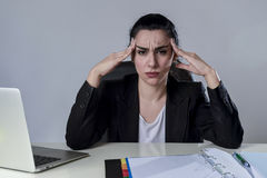 Business woman working on laptop at office in stress suffering intense headache migraine Stock Image