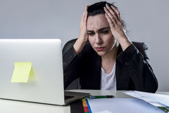 Business woman working on laptop at office in stress suffering intense headache migraine Royalty Free Stock Photo