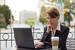 Business woman working on laptop at outdoor coffee shop Royalty Free Stock Image