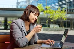 Business woman working on laptop at outdoors cafe Royalty Free Stock Images