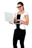 Business woman working on laptop. Smiling corporate lady browsing on her laptop Royalty Free Stock Image