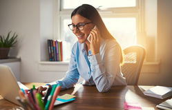 Business woman working on laptop. Smiling talking on phone sun coming through window Royalty Free Stock Photography