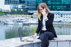 Business woman working on laptop and talking on the phone on the background of skyscrapers Stock Images