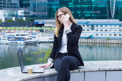 Business woman working on laptop and talking on the phone on the background of skyscrapers Royalty Free Stock Photos