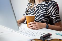 Business woman working in minimalistic office. Young female person with coffee in front of desktop computer at modern workplace stock photography
