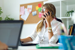 Business woman working with mobile phone in her office. Stock Photos