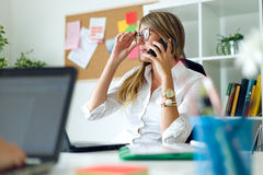 Business woman working with mobile phone in her office. Royalty Free Stock Photos