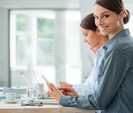 Business woman working at office desk with her colleagues Stock Photos