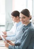Business woman working at office desk with her colleagues Stock Image