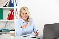 Business woman working in office with documents. Beautiful middle aged woman looking at camera with smile while siting Royalty Free Stock Images