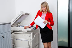 Business woman working on office printer. Attractive blond business woman working on office printer machine Royalty Free Stock Photography